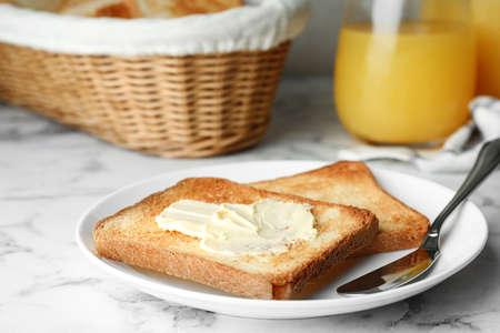 Kromki chleba tostowego z masłem na białym marmurowym stole