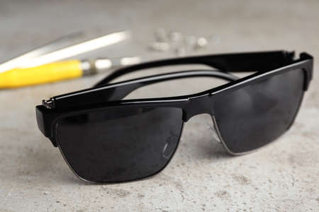 Stylish sunglasses and fixing tools on grey table