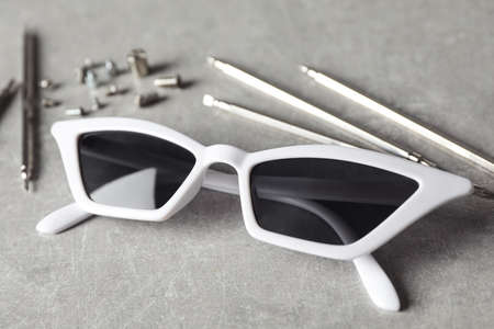 Stylish female sunglasses and fixing tools on grey table 写真素材