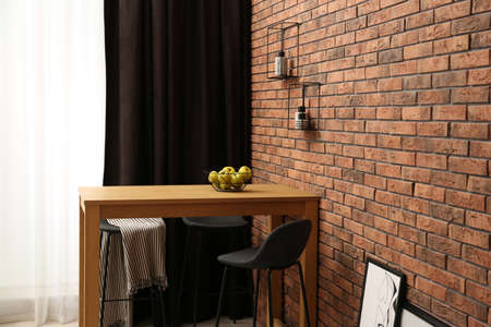 Elegant room interior with wooden table near brick wall