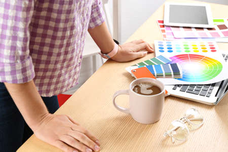 Woman working with palette samples at wooden table, closeup