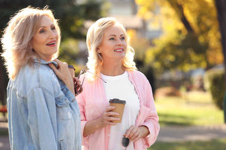 Happy mature women with coffee in park on sunny day Stock Photo