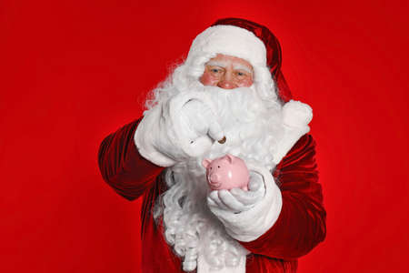 Santa Claus putting coin into piggy bank on red background