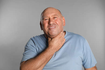 Mature man suffering from throat pain on light grey background Stock Photo