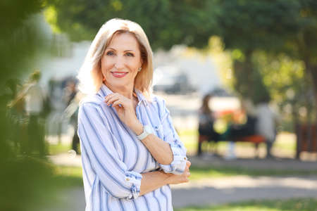Portrait of happy mature woman in park on sunny day Stock Photo