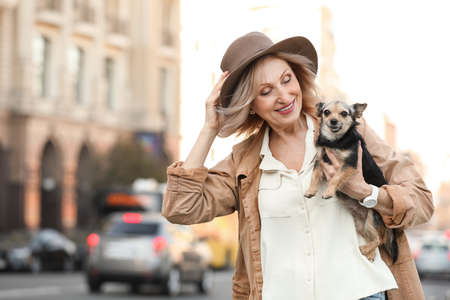 Beautiful mature woman with cute dog on city street Stock Photo