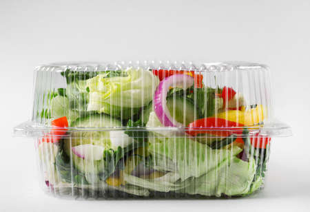 Plastic container with fresh salad on light grey background