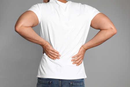 Man suffering from backache on light grey background, closeup Stock Photo