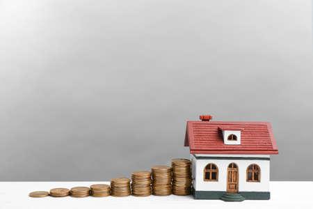 밝은 회색 배경에 흰색 나무 테이블에 집 모델과 동전. 돈 절약 스톡 콘텐츠