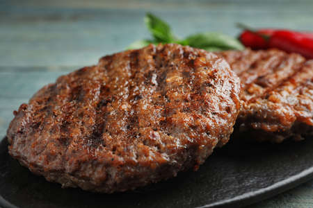 Grilled meat cutlets for burger on blue wooden table, closeup Stock Photo