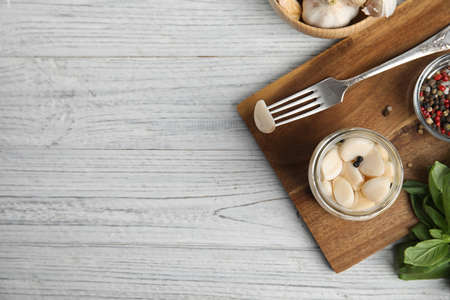 Flat lay composition with jar of pickled garlic on white wooden table. Space for text Stock fotó