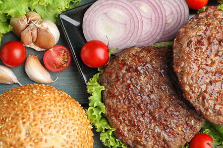 Grilled meat cutlets and ingredients for burger on blue wooden table, top view