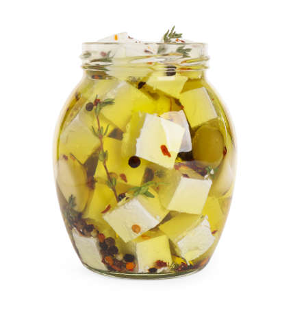 Open jar with feta cheese marinated in oil on white background. Pickled food