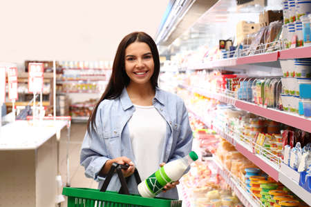Young woman with shopping basket in supermarket
