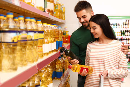 Young couple with shopping basket in supermarket Stock Photo