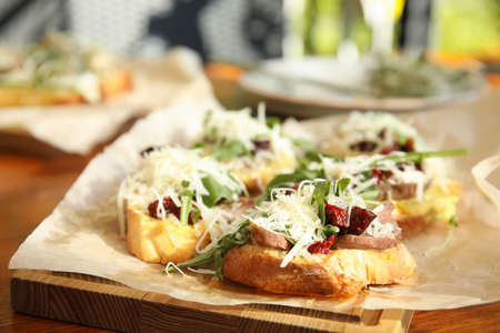 Delicious bruschettas with beef and cheese on table
