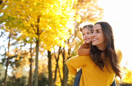 Happy woman with little daughter in sunny park. Autumn walk Stock Photo