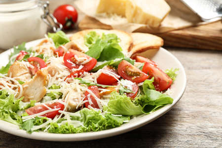 Delicious fresh Caesar salad on wooden table, closeup