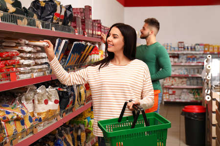 Young woman with shopping basket in supermarket Stock Photo - 133697261