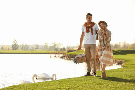 Young couple with picnic basket near lake on sunny day