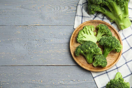 Fresh green broccoli on wooden table, flat lay. Space for text