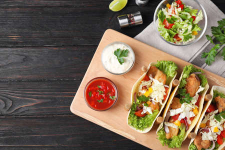 Delicious fish tacos served on dark wooden table, flat lay