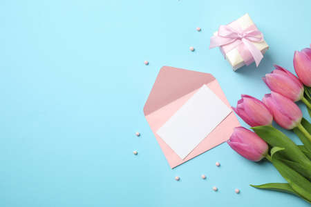 Flat lay composition with tulips and card on light blue background, space for text. Happy Mothers day Stock Photo