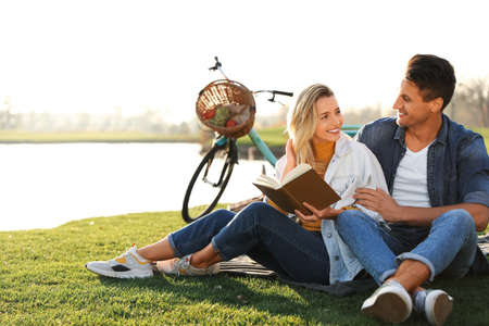 Happy young couple reading book while having picnic outdoors