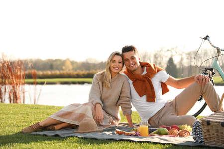 Happy young couple having picnic near lake on sunny day Archivio Fotografico