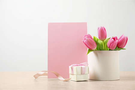Blank greeting card, tulips and gift on table, space for text. Happy Mothers day
