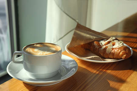 Taza de café aromático fresco y croissant en la mesa del café