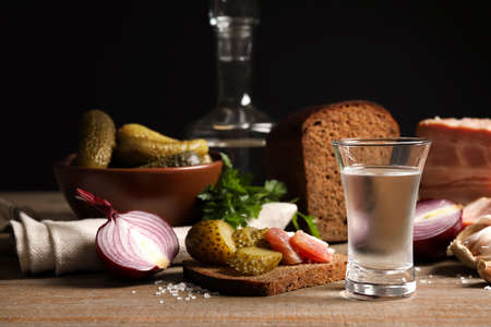 Kalter russischer Wodka mit Snacks auf Holztisch Standard-Bild