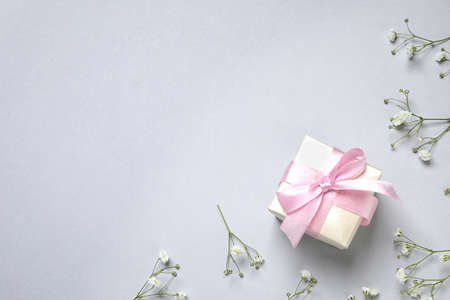 Flat lay composition with flowers and gift on light grey background, space for text. Happy Mothers day