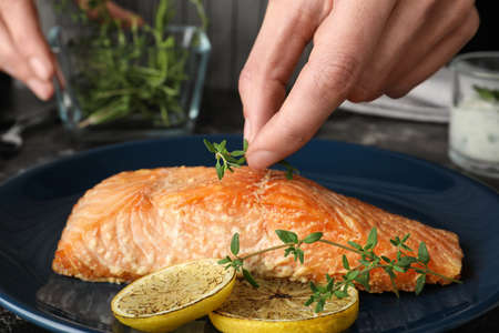 Woman adding thyme to cooked red fish on table, closeup Stock fotó