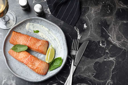 Tasty cooked red fish on dark marble table, flat lay. Space for text