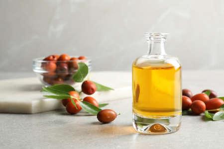 Jojoba oil in glass bottle and seeds on light grey table