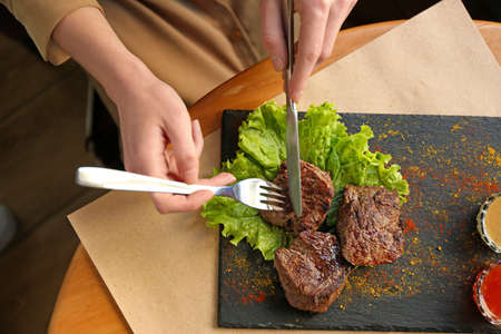 Woman eating tasty shish kebab in cafe