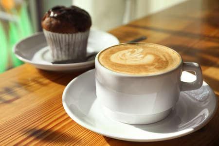 Taza de café aromático fresco y cupcake en la mesa de café