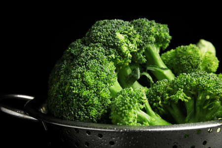 Fresh green broccoli in colander on black background, closeup
