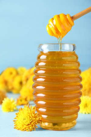 Miel savoureux et fleurs de chrysanthème sur table bleu clair