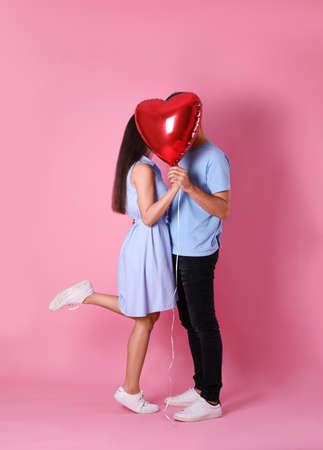 Lovely couple hiding behind heart shaped balloon on pink background. Valentine's day celebration