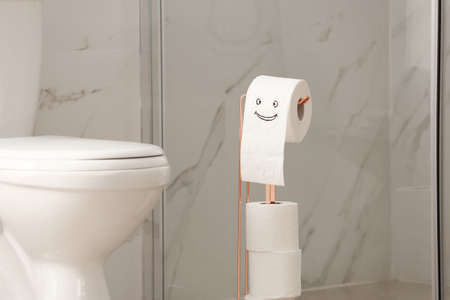 Modern toilet bowl and paper with funny face in bathroom