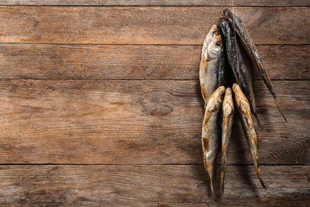 Pescado seco colgando de una cuerda contra el fondo de madera, espacio para texto