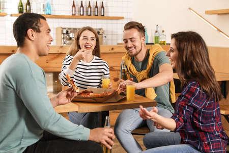 Gruppo di amici che si divertono a una festa con una deliziosa pizza al caffè