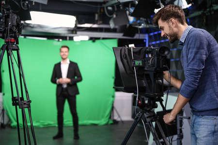 Presentador y operador de cámara de video trabajando en estudio. Difusión de noticias