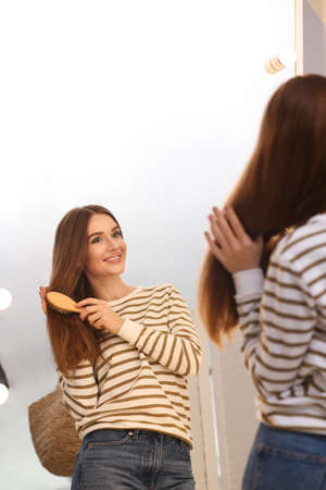 Beautiful young woman with hair brush looking at herself in large mirror indoors