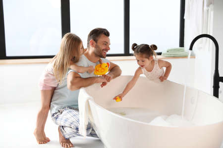 Young father with little daughters in bathroom
