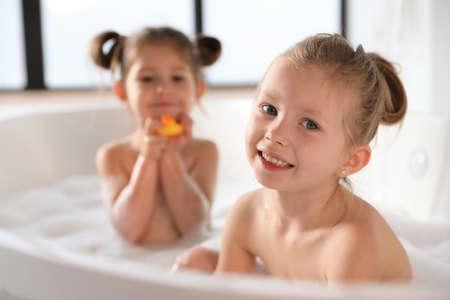 Petites soeurs mignonnes prenant un bain moussant ensemble