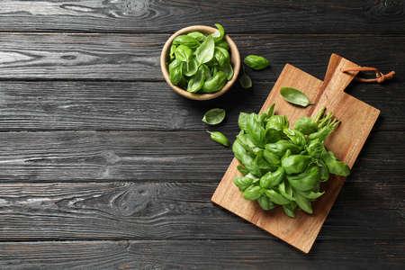 Albahaca verde fresca sobre mesa de madera negra, plano laical. Espacio para texto