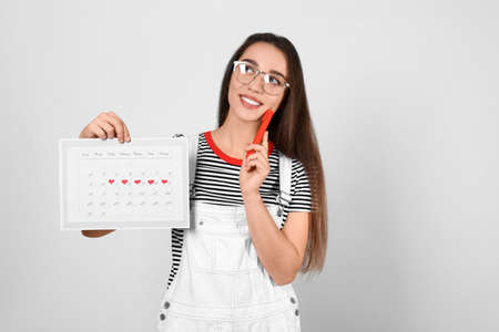 Young woman holding calendar with marked menstrual cycle days on light background